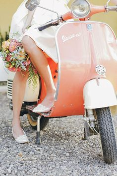 Wedding with a bride sitting on a Vespa scooter on a gravel road. gideonphoto.com