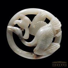 鶻啄鵝飾件 宋 遼金時期 長8.3、寬7.6厘米 器以圓環為托高浮雕、鏤雕鶻捉天鵝圖案。天鵝體形肥碩,曲頸仰天悲鳴,正在拼命掙扎。鶻身形雖小,但勇猛矯健,雙爪有力地抓住天鵝頭部,短喙銳利地伸向鵝的顱頂。這種只雕刻鶻、鵝,沒有花草雜飾的造型是早期春水玉特徵,圓環托至元也演變為橢圓形。 Chinoiserie, Asian Art Museum, Antique Jade, White Jade, Chinese Culture, Jade Pendant, Ancient Civilizations, Stone Carving, Ancient Art