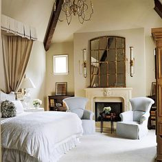 Relaxed and Refined - Rustic beams, a stone mantel, and plaster walls temper this master bedroom's dramatic cathedral ceiling with their earthy elegance. A floating canopy soars with the architecture, while a serene palette helps keep the space relaxed.