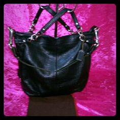 Black leather Authentic Coach purse. Like new! Black coach purse! Very soft Pebbled leather, and silver hardware. Has two handles with silver chains and a detachable shoulder strap. Inside is a purple silk lining. Euc. No flaws! One of my favorite coach bags!   BUY ONE GET ONE HALF OFF that's equal to or lesser than in value!   Feel free to make a offer on any of my item's!   Thanks for looking! Coach Bags Shoulder Bags