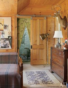 At a Tennessee farmhouse decorated by Suzanne Kasler, a boy's room features wood-paneled walls and a Tibetan rug from Tufenkian.