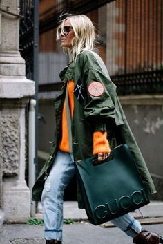 A khaki anorak is paired with an orange sweater, distressed jeans and an oversized Gucci handbag