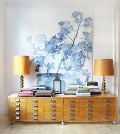 Low vintage drawers with tall lamps and a large art work to handle the high ceiling