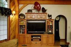 An entertainment center really ties this room together by incorporating the same wood species and stain that's been used elsewhere in the room. Bead board backing and integrating the baseboard ventilation into the toe of the cabinet are finishing touches that make this a focal point worthy of any living room or den.  #wood #stained #paneled #matching #remodel #family #room #entertainment #center #tv #television #surround #storage #country #rustic #custom #den #living