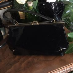 "Vintage 50's JR Black Patent Vinyl Handbag This beautiful and classy Vintage Black Patent Vinyl Handbag features a brass-tone closure and top hardware trimmed in black patent, decorative side straps with brass-tone studs, and matching protective stud feet on bottom. Measures 12"" wide x 6-1/2"" tall (add 4"" for handle) x 4"" deep. Inside lined in black leatherette with a clear plastic zippered compartment stamped in gold 'JR.' In excellent preowned vintage condition. Smoke-free home. Vintage…"
