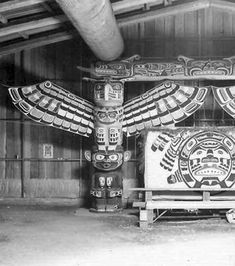 The interior of the  Big House, Cormorant Island showing a Thunderbird, the eagle figure at the top of the pole, supported by Dzunuk'wa with her characteristic lips. Photo: © Adelaide de Menil, 1967