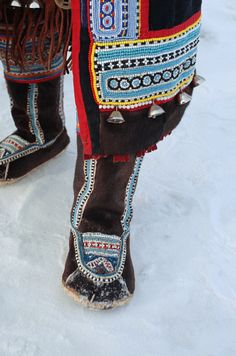 An Even woman wearing a pair of traditional reindeer skin boots decorated with bead work. Evensk, Magadan, E. Siberia