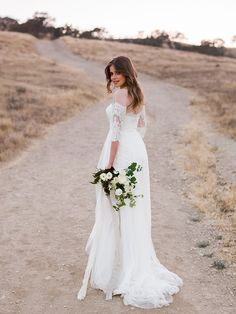 Lace details give the illusion of an off-the-shoulder neckline on this sheath wedding dress with sleeves. Exclusively at David's Bridal. Photo by Braedon Flynn.