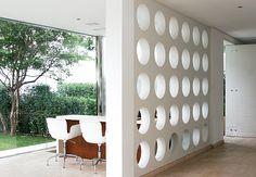 A parede que fechava a visão da sala na entrada deste apartamento foi substituída pelo painel com círculos de madeira laqueada. O projeto é do designer de interiores Francisco Cálio