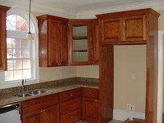 Granite countertop, prefab cabinets that wrap around a refrigerator.