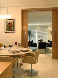 A porta de correr de madeira e o piso em mármore ligam a sala de almoço a de jantar na proposta da ARZ Design para a família que recebe muitos amigos em casa. Do lado do almoço, a composição da mesa Saarinen em mármore de Carrara com as cadeiras Tulipa