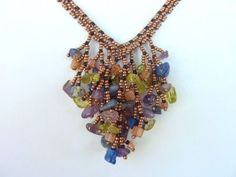 DIY Jewelry: FREE beading pattern for lovely V-shaped necklace made using coraling technique with 11/0 and 15/0 seed beads and multi-colored drilled chips.
