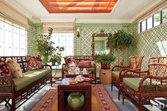 The rooftop solarium is appointed with a trellis-pattern wall covering by Brunschwig & Fils, a suite of bamboo furniture from Red Egg, and a pair of Jasper tables.