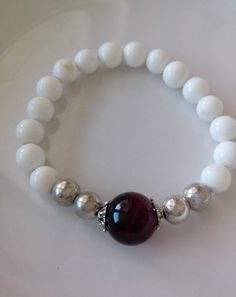 This is a beautiful mala bracelet. The beads are 8mm white pearl shell. The beads have asuper glossy shine and it is amazing. The center bead is a red colored Tiger eye bead. The bead is 14mm and the