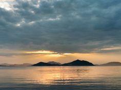 ( Evening Now at Hakata bay in Japan) 16 July 19:03 雨上がりの博多湾対岸、糸島半島の稜線に夕暮れの光が広がっています。