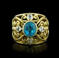 Crevoshay Pierced Band Cambodian Blue Zircon Ring A bezel set 6.38 carat oval Cambodian blue Zircon is flanked by two emerald cut and two...