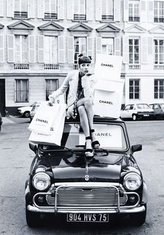 Christy Turlington personifies luxury as she sits atop a Mini Cooper with her legion of shopping bags wearing a ruffle sleeved button down tweed blazer as part of her head-to-toe Chanel attire in the editorial 'Rive Paris!' shot by longtime friend of the model photography legend Steven Meisel for Vogue Italia February 1992.