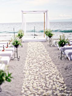 Getting married by the water? Instead of hiding the sand under a runner, play up your beachy atmosphere by lightly lining your aisle with petals or greenery. Shoes are overrated anyways, right? Photo via The Wedding Scoop .