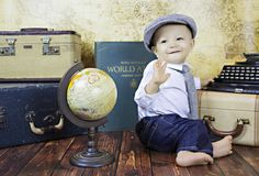 This little traveler is ready to explore, with vintage luggage, atlas and mini globe from American Vintage Rentals | Childrens Photography | Vintage Photo Shoot Photo by Zsavonne Photography zzsavonne@gmail.com