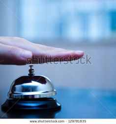 Hand ringing in service bell on wooden table. by hxdbzxy, via ShutterStock