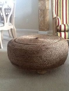 "I upcycled a 26"" used tire into an Ottoman !!!!     This is my upcycled ottoman, i made it with an old 26"" tire, plywood, glue, manila rope in a round design, in the center a Gentleman's Jack bottle cap, all of these items were recycled items ( except the manila rope) and added fence caps as legs for extra savings"
