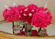 wedding picture idea-Hot pink open roses with stephanotis (jewel in center of stephanotis). Stem in ribbon of rhinestones. Pink hydrangeas for the bridesmaids with a black ribbon stem and pearls down them. Taken on an old vintage mirror.