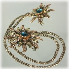 Van Dell gold filled layered flower sweater guard pins. Done in gold and rose gold, the pins shine and shimmer. Each is highlighted with an aqua