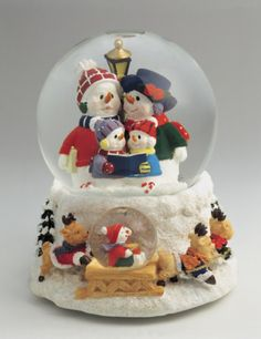 Close-up of figurines of a snowman family in a snow globe