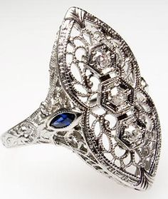 Antique Art Deco Dinner Ring North to South Style Solid 18K White Gold 1930's. This lovely antique art deco dinner ring is crafted of solid 18k white gold and features three old mine cut diamonds and two created blue sapphires. This ring has ornate filigree and is in good condition. Via Era Gem.