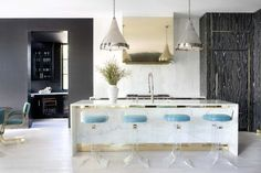 cocina americana, bonito ejemplo de cocina con barra y sillas modernas de plástico transparente y asientos azules, lámparas y campana extractora en estilo industrial