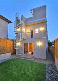This stunning contemporary home exterior opens up to a lush backyard and has a spiral staircase that leads up to the roof.