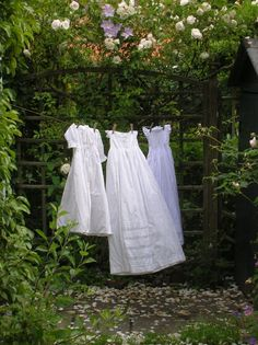 Ana Rosa - 3 white vintage dresses hanging on a clothesline