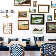 Gallery wall made up of vintage oil paintings at Paper Daisy restaurant inside Halcyon House. Sconce and bistro chairs by Serena & Lily