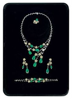 AN EMERALD AND DIAMOND PARURE, BY ELIE CHATILA.  Earrings, ring and bracelet en suite.