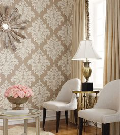 damask beige wall paper, white matching chairs, pedistool side tables, large rose arrangement, gold curtains, sunburst mirror