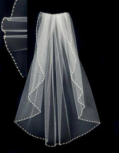 Trios of pearls and clear seed beads embellish the edge of this waist length wedding veil. Perfect pearls for your wedding! It is 30 inches long and 72 inches