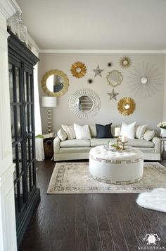 Kelley Nan: Formal Living Room Tour- Gold and Silver Sunburst Mirror Gallery Wall in Formal Living Room - Perfect Greige by Sherwin Williams - Neutral and White Sitting Room with Black Restoration Hardware French Casement Cabinet and white tufted ottoman form My Chic Nest
