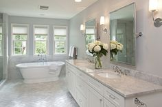 Dura Supreme painted white cabinetry and Carrara Marble Herringbone floor, wall tile and countertops are shown here in this traditonal white bathroom.