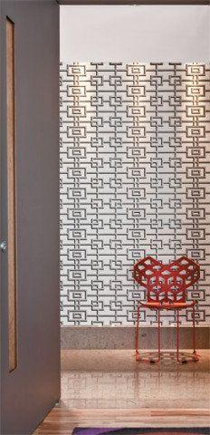 """A designer de interiores Adriana Penteado assina este hall do elevador, queganhou um papel de parede de desenho geométrico (modelo Rheinsberg,da Designers Guild, encontrado no Empório Beraldin). """"O efeito marcanteque os moradores desejavam foi garantido pela padronagem dorevestimento, associada à iluminação embutida no forro de gesso"""", explicaAdriana. A cadeira Dazzle (A Lot Of), com seu encosto recortado, completa acena."""