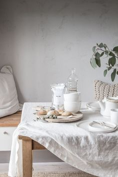 A neutral and relaxed table setting with white linens and gray walls.