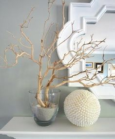 Modern Coastal - eclectic. Driftwood branch and sand in glass bowl with moroccan style mirror.