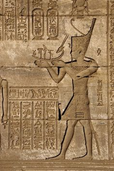 Ancient Egyptian sunken relief depicting man carrying a symbolic bark, detail of a Roman mammisi, in Denderah, built under the reign of Pepi I (ca. 2250 BC)