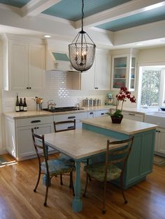 Charming kitchen with country blue island Blue beadboard accents run from the island to the ceiling to the range hood. A lovely combination with white cabinetry.