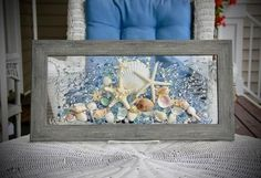 This Sea Glass Art is a beautiful piece that is ready to great to hang on a wall or a window! Any beach lover would treasure this piece forever.  The shells are bonded onto the glass with resin. The faux wood frame, measures approximately 22 x 11, and is drift wood grey in color.  Among the Coastal Wall Art, Coastal Decor, Blue Wall Decor, Heart Wall Art, Selling Handmade Items, Coastal Bathrooms, Sea Glass Art, Window Art, New Art