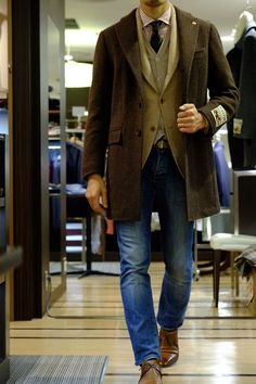 Wear a dark brown overcoat with blue jeans to create a dressy but not too dressy look. Dress it up with brown leather derby shoes. Shop this look for $426: http://lookastic.com/men/looks/jeans-and-derby-shoes-and-dress-shirt-and-tie-and-overcoat-and-cardigan-and-blazer/610 — Blue Jeans — Brown Leather Derby Shoes — Burgundy Vertical Striped Dress Shirt — Black Tie — Dark Brown Overcoat — Beige Cardigan — Beige Wool Blazer