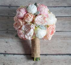 A soft and elegant wedding bouquet with ivory, peach, and blush peonies, garden roses, and ranunculus, accented with soft green lamb's ear. This wedding bouquet is wrapped in burlap ribbon, but can be customized to coordinate with your wedding colors. This bouquet measures 10 inches wide and 12 inches tall. Smaller bridesmaids bouquets or toss bouquets can be made to order. Kate Said Yes is having a baby! Right now we are accepting orders for September weddings and beyond. Please contact....