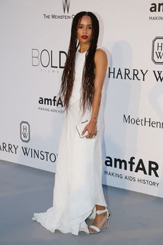 Zoe Kravitz in a white dress, white heels, and white clutch