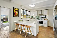 Bright white kitchen and warm natural tile floor