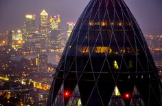 london's iconic gherkin building and the towers of the Canary Wharf business district