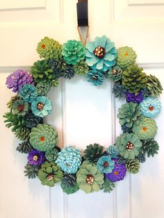 Hand painted pine cone wreath mimicking succulent colors. Pine cones are wired to wreath frame enabling it to be used outside but preferably under a covered porch. Rain can damage pine cones. Wreath is 13.5 x 13.5.
